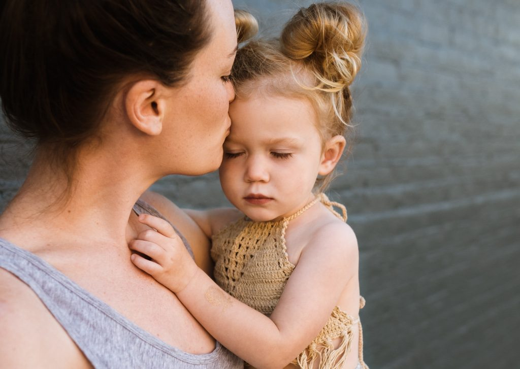 mom kissing child setting boundaries shame